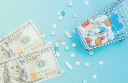 mini shopping cart with pills spilling out onto cash