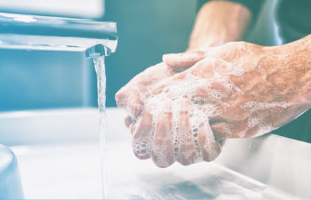 man washing hands at sink